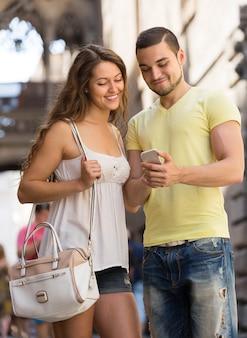 Pareja usando el mapa en el teléfono inteligente