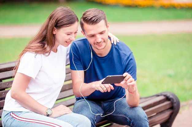 Pareja usando tableta y teléfono celular en parque público.