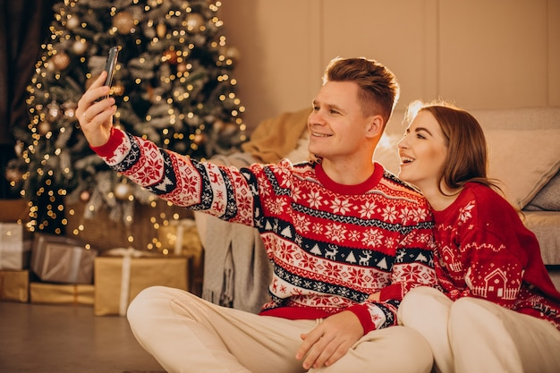 Pareja usando el teléfono juntos en navidad