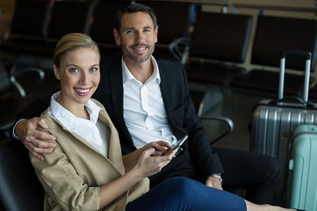 Pareja, utilizar, teléfono móvil, en, aeropuerto