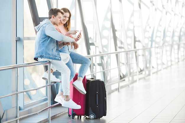 Pareja viajando. viaje de los amantes. joven hombre y mujer en el aeropuerto. tour familiar