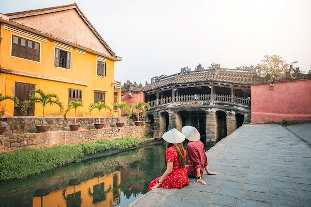 Pareja de viaje con puente cubierto japonés, en hoi an, vietnam
