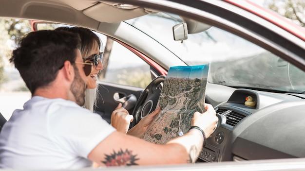 Pareja de viaje sentado en el coche mirando el mapa