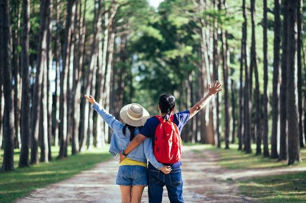 Una pareja viajera en bosque de pinos