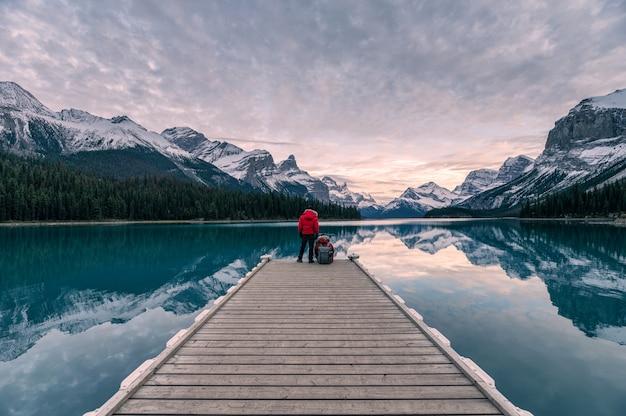 Pareja viajera relajante en el muelle de madera en el lago maligne en spirit island, parque nacional jasper