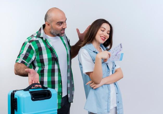 Pareja de viajero adulto impresionado hombre sosteniendo maleta mirando a mujer manteniendo la mano en el aire y mujer feliz sosteniendo y mirando boletos de viaje