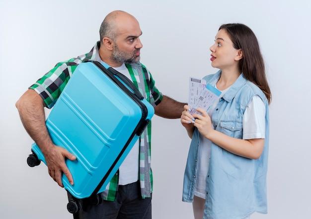 Pareja de viajeros adultos con el ceño fruncido hombre sujetando la maleta manteniendo la mano en el aire impresionado mujer sosteniendo billetes de viaje mirando el uno al otro