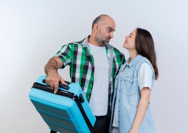 Pareja de viajeros adultos complacido hombre sujetando la maleta y mujer sonriente mirando el uno al otro