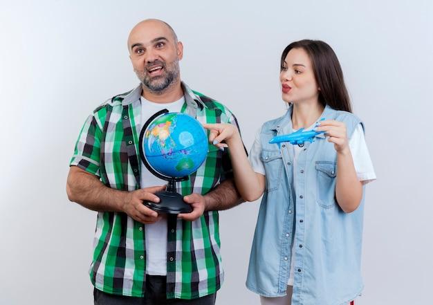Pareja de viajeros adultos impresionado hombre sosteniendo globo mirando recto y complacido mujer sosteniendo avión modelo mirando globo y tocándolo