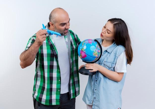 Pareja de viajeros adultos impresionado hombre sujetando modelo de avión y mujer haciendo gesto de beso sosteniendo globo tanto mirando globo