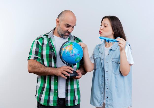 Pareja de viajeros adultos impresionados hombre sosteniendo globo y mujer sosteniendo avión modelo tocando globo y ambos mirando globo