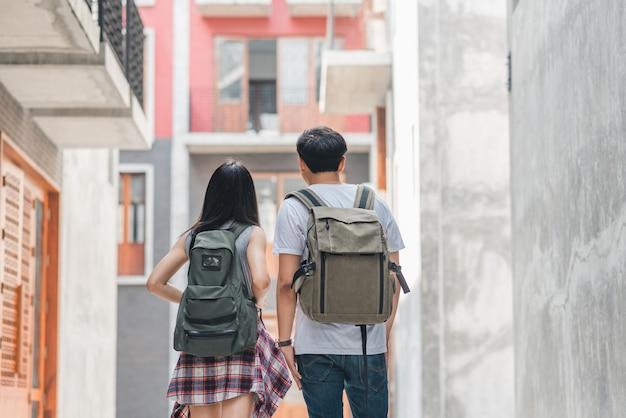 Pareja de viajeros asiáticos mochileros que sienten felices viajando en beijing, china, alegre joven pareja caminando en chinatown.