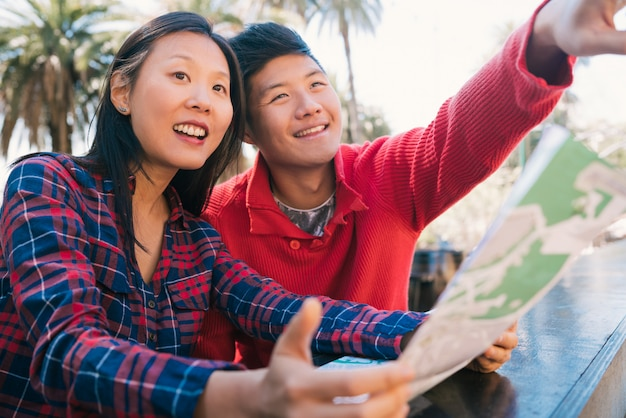 Pareja de viajeros asiáticos sosteniendo un mapa y buscando direcciones.