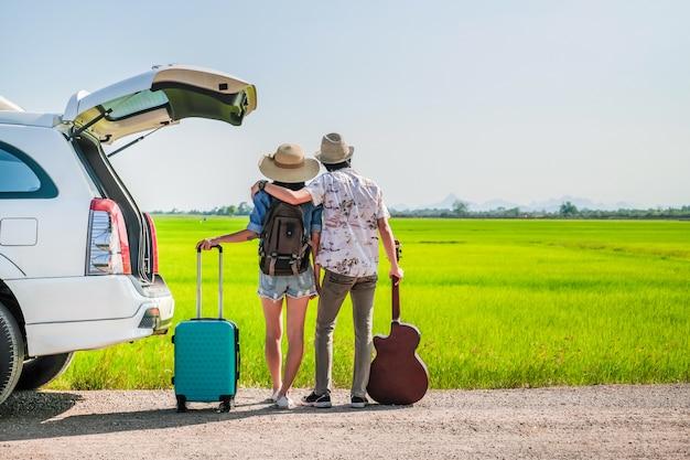 Pareja de viajeros tienen equipaje y guitarra de pie cerca de un coche
