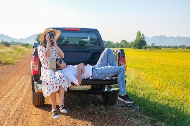 Pareja de viajeros tienen un tiempo de relax durante el viaje al lado de la carretera.