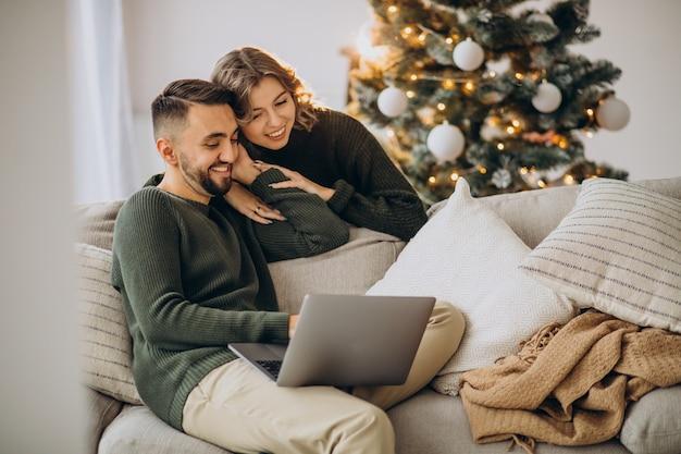 Pareja en videollamada con ordenador portátil el día de navidad