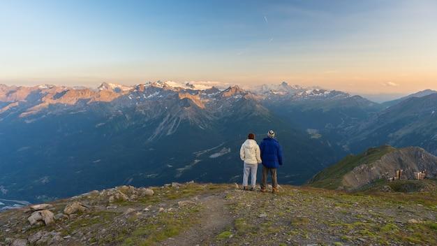 Pareja viendo panorama en lo alto de los alpes