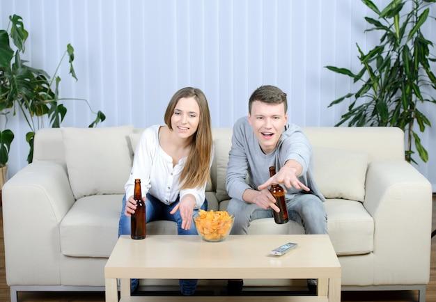 Pareja viendo la televisión y bebiendo cerveza en casa en la sala de estar.