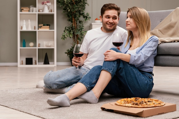 Pareja viendo la televisión y bebiendo vino