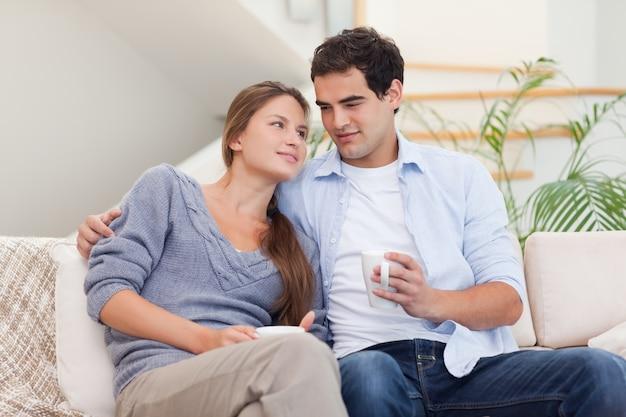 Pareja viendo la televisión mientras bebe café