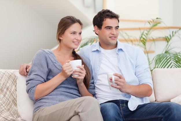 Pareja viendo la televisión mientras bebe té