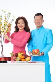 Pareja vietnamita en ropas tradicionales brillantes posando en estudio con frutas y flores.