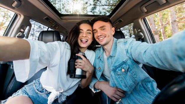 Pareja de vista frontal tomando selfie en coche