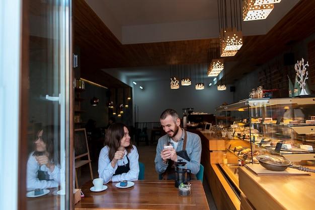 Pareja vistiendo delantales en cafetería