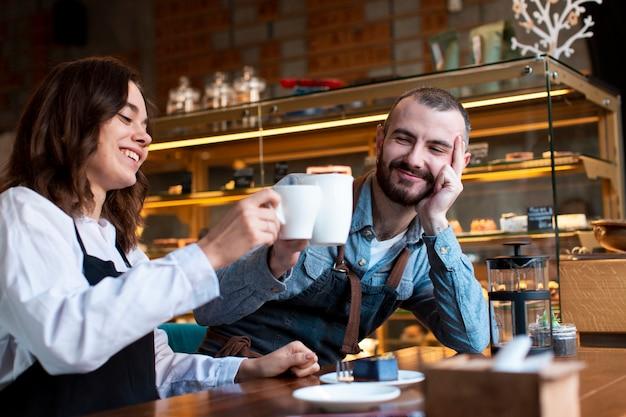 Pareja vistiendo delantales tomando un café en la tienda