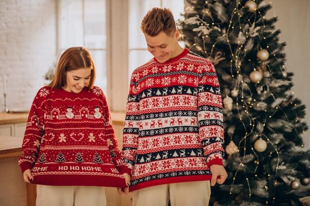 Pareja vistiendo suéteres de navidad juntos