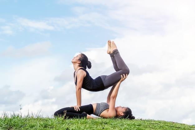 Pareja yoga mujer pose en hierba verde contra el cielo azul