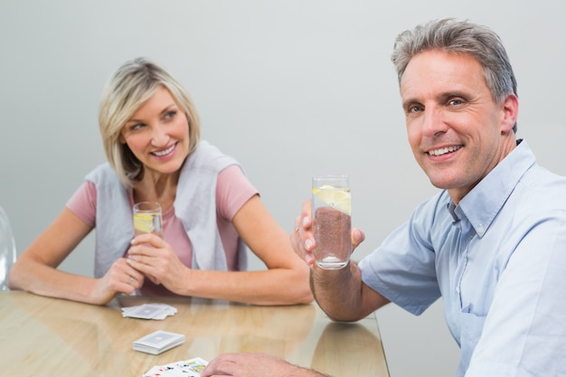Pareja con zumos de lima jugando a las cartas en casa