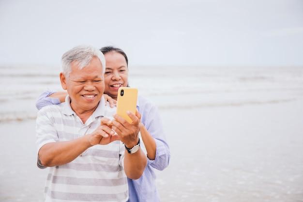 Las parejas ancianas asiáticas usan teléfonos inteligentes para selfie en la playa junto al mar