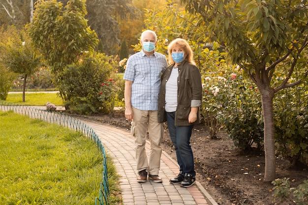 Las parejas ancianas caminando afuera con máscaras médicas