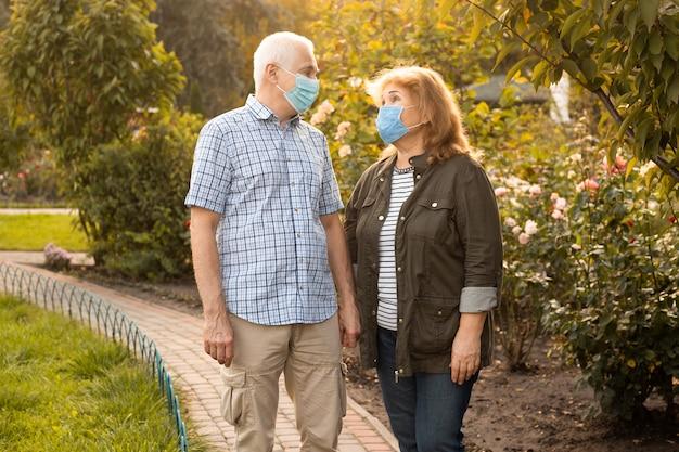 Las parejas ancianas caminando afuera en la naturaleza con máscaras médicas