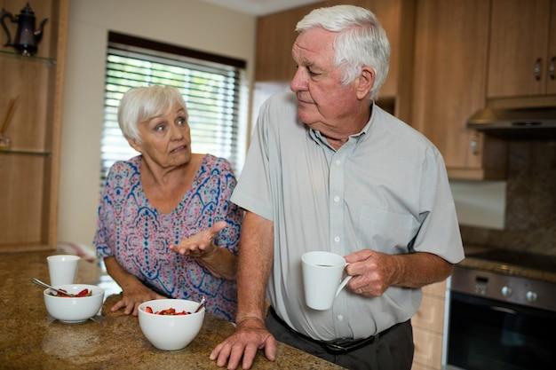 Las parejas ancianas discutiendo en la cocina de casa