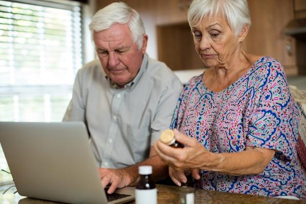 Las parejas ancianas con laptop y sosteniendo el frasco de pastillas en la cocina de casa