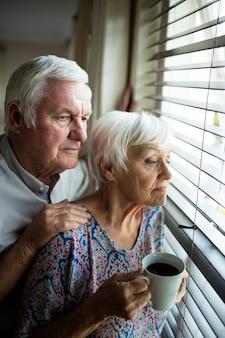 Las parejas ancianas mirando desde la ventana en casa