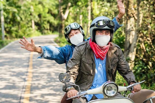 Las parejas ancianas montando un scooter en nuevos viajes normales
