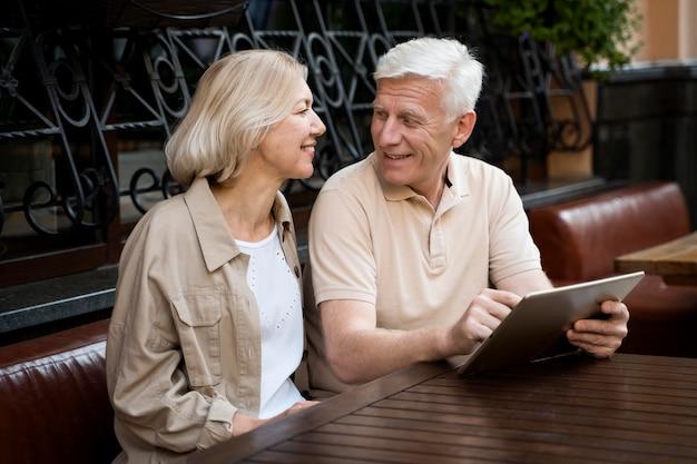 Las parejas ancianas sentadas mientras están en la ciudad con tableta