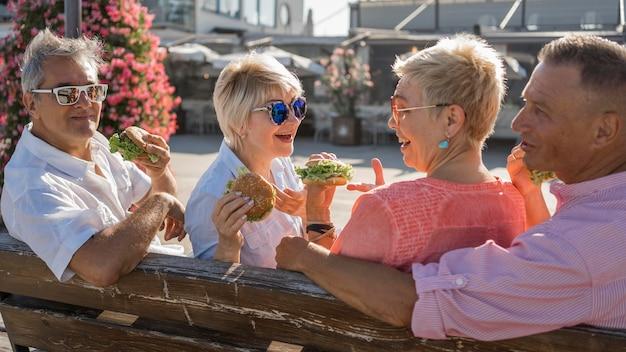 Parejas de ancianos comiendo hamburguesas en la playa