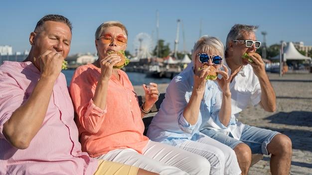 Parejas de ancianos disfrutando de hamburguesas juntos en la playa