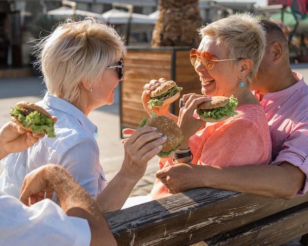 Parejas de ancianos disfrutando de hamburguesas en la playa