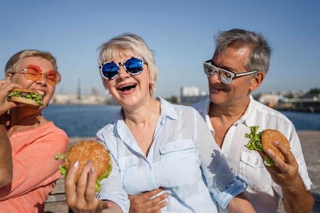 Parejas de ancianos en la playa disfrutando de hamburguesas