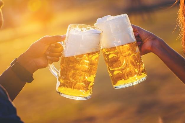 Parejas animando cerveza de barril con el sol
