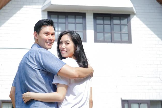 Las parejas asiáticas masculinas y femeninas se paran, se abrazan y sonríen felices frente a la nueva casa. el concepto de iniciar una vida matrimonial para crear una familia feliz. copia espacio