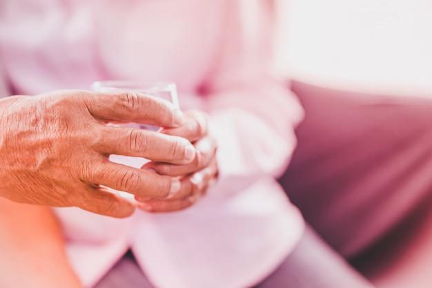 Las parejas asiáticas mayores toman la píldora con un vaso de agua, enfoque selectivo
