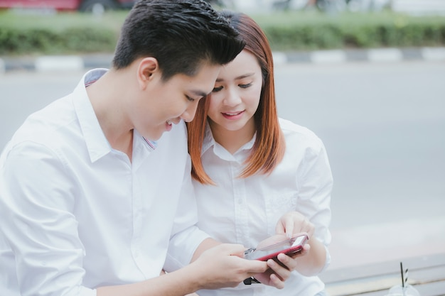 Parejas asiáticas revisando el teléfono juntos mientras están sentados en la silla junto a la carretera. día de san valentín