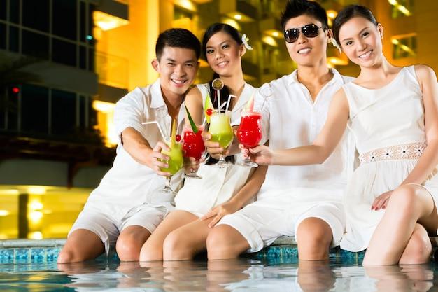 Parejas chinas bebiendo cócteles en el bar de la piscina del hotel