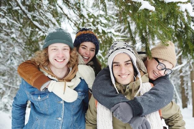 Parejas felices en bosque de invierno